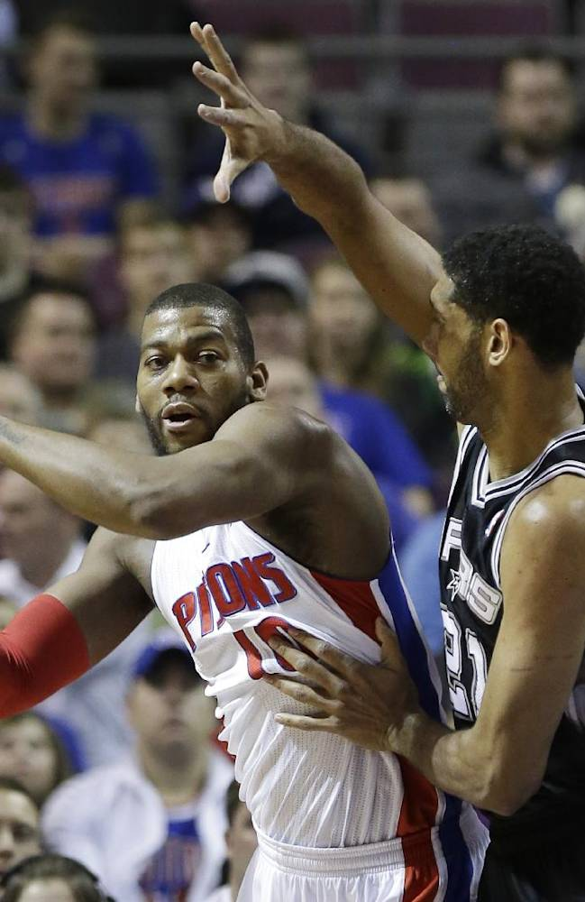 Detroit Pistons forward Greg Monroe (10) passes the ball as he is defended by San Antonio Spurs forward Tim Duncan (21) during the first half of an NBA basketball game in Auburn Hills, Mich., Monday, Feb. 10, 2014