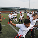 Oakland Raiders Marcel Reece, left, plays football with children during an event at Guildford, England, Tuesday, Sept. 23, 2014. The Raiders will play the Miami Dolphins in an NFL football game at London's Wembley Stadium on Sunday Sept. 28. The Associate