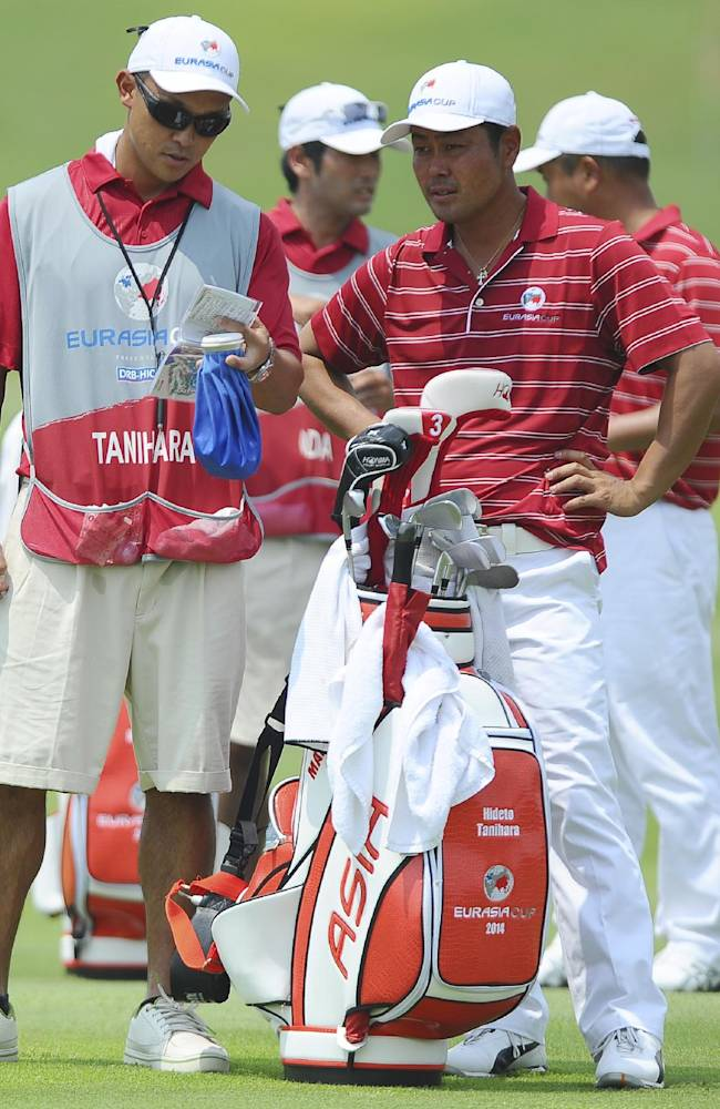 Japan's Hideto Tanihara, right, consults with his caddy before his shot on the 10th hole during the second round of the EurAsia Cup golf tournament at the Glenmarie Golf and Country Club in Subang, Friday, March 29, 2014