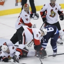 Ottawa Senators' Colin Greening (14), Cody Ceci (5) and Winnipeg Jets' Michael Frolik (67) get tangled up in front of Senators goaltender Craig Anderson (41) and Chris Phillips (4) during the third period of an NHL hockey game, Saturday, March 8, 2014 in