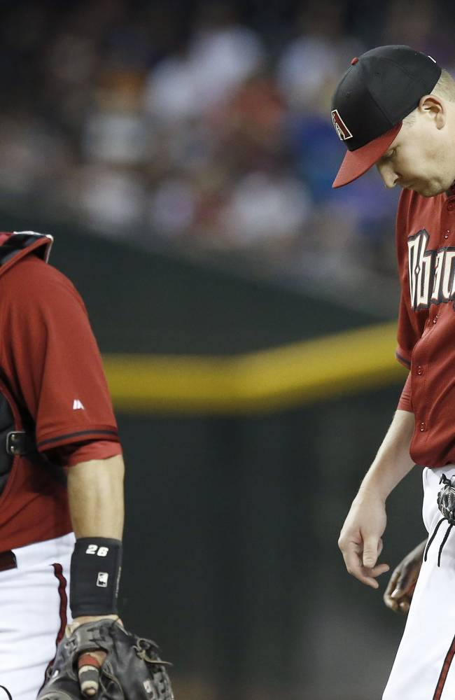 Arizona Diamondbacks' Trevor Cahill, right, looks down after getting a visit from catcher Miguel Montero after Cahill gave up a run to the Chicago Cubs in the fourth inning of a spring training baseball game, Friday, March 28, 2014, in Phoenix