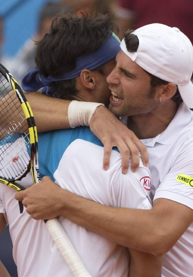 Italy's Simone Bolelli, right, embraces teammate Fabio Fognini after they defeated Argentina in a doubles tennis match, giving Italy a 2-1 lead at the Davis Cup tournament in Mar del Plata, Argentina, Saturday, Feb. 1, 2014