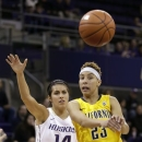 California's Layshia Clarendon, right, passes into the key as Washington's Heather Corral defends in the first half of an NCAA college basketball game Saturday, March 2, 2013, in Seattle. (AP Photo/Elaine Thompson)