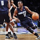 Charlotte Bobcats point guard Kemba Walker (15) drives to the basket as center Bismack Biyombo (0) picks Brooklyn Nets forward Alan Anderson in the second half of an NBA basketball game Wednesday, Feb. 12, 2014, in New York. The Nets won 105-89 The Associ