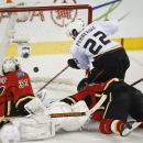 Anaheim Ducks' Mathieu Perreault, right, scores as Calgary Flames goalie Karri Ramo, left, from Finland, and Ladislav Smid, from the Czech Republic, look on during third period NHL hockey action in Calgary, Alberta, Wednesday, March 26, 2014. The Anaheim
