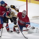 Montreal Canadiens goalie Carey Price, right, gloves the puck as Canadien's defenseman Tom Gilbert hangs on to Boston Bruins' Carl Soderberg during first-period NHL hockey game action Thursday, Oct. 16, 2014, in Montreal The Associated Press