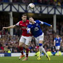 Everton's Ross Barkley, right, fights for the ball against Arsenal's Thomas Vermaelen during their English Premier League soccer match at Goodison Park Stadium, Liverpool, England, Sunday April 6, 2014