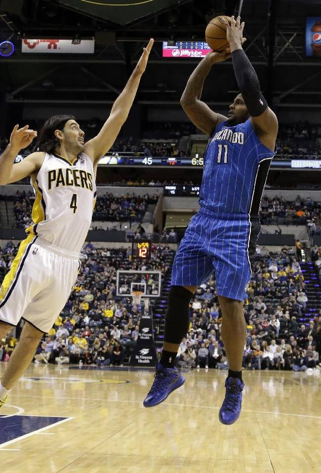 Orlando Magic forward Glen Davis, right, pulls up for a shot over Indiana Pacers forward Luis Scola in the first half of an NBA basketball game in Indianapolis, Monday, Feb. 3, 2014