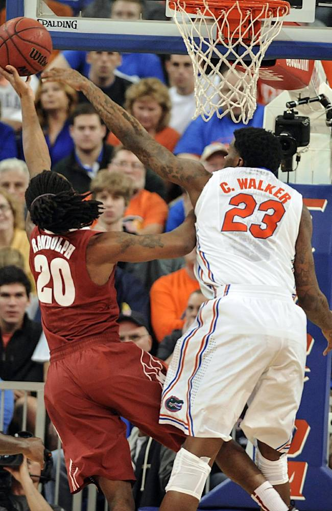 Florida's Chris Walker (23) tries to blocks shot by Alabama guard Levi Randolph (20) but fails during the first half of an NCAA college basketball game Saturday, Feb. 8, 2014, in Gainesville, Fla