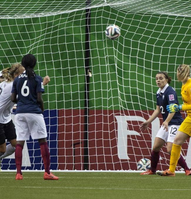The ball goes into the net past France goalkeeper Solene Durand on a goal by Germany's Lena Petermann during the second half of a FIFA U-20 women's World Cup semifinal in Montreal on Wednesday, Aug. 20, 2014. Germany won 2-1