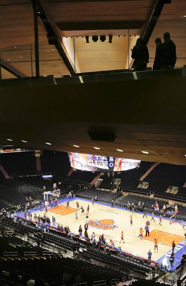 Pedestrians move across one of two Chase Bridges while teams warm up before an NBA basketball game between the New York Knicks and the Charlotte Bobcats, Friday, Oct. 25, 2013, in New York