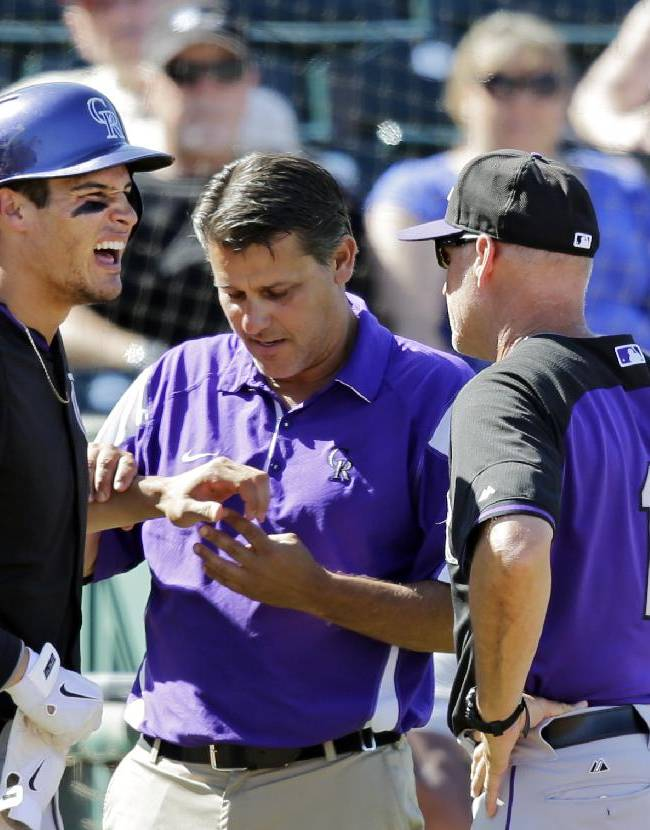 Colorado Rockies' Nolan Arenado, left, is check head trainer Keith Dugger and bench coach Tom Runnells (11) after being hit in the hand by a pitch from Cleveland Indians starting pitcher Corey Kluber in the sixth inning of a spring exhibition baseball game Saturday, March 22, 2014, in Goodyear, Ariz. Arenado left the game after the injury