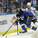 St. Louis Blues' Jay Bouwmeester, left, and Chicago Blackhawks' Jonathan Toews, right, battle for the puck during the first period in Game 2 of a first-round NHL hockey playoff series on Saturday, April 19, 2014, in St. Louis. (AP Photo/Bill Boyce)