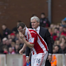 Stoke's Charlie Adam takes to the field wearing a protective face mask as manager Mark Hughes looks on during his team's English Premier League soccer match against Newcastle United at the Britannia Stadium, Stoke, England, Saturday April 12, 2014