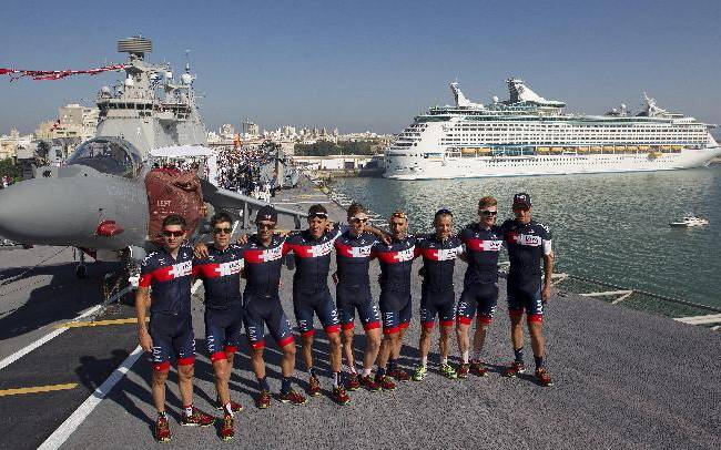 IAM Cycling Team pose in front of the Prncipe de Asturias aircraft carrier, the only one in the Spanish navy's possession, at the start of the third stage of the Vuelta, tour of Spain cycle race, in Cadiz, Spain, on Monday Aug 25, 2014. The third stage of the Spanish Vuelta cycling race over 188 kilometers will start in Cadiz and finish in Arcos de La Frontera