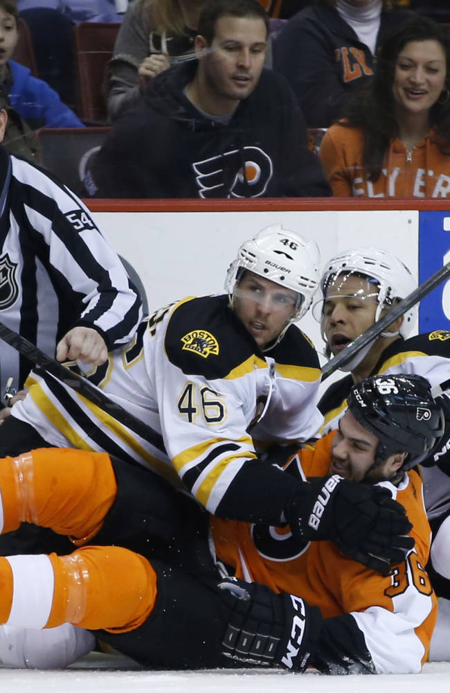 Boston Bruins' Jarome Iginla (12) and David Krejci, of the Czech Republic, collide with Philadelphia Flyers' Zac Rinaldo (36) and linesman Greg Devorski (54) during the first period of an NHL hockey game on Sunday, March 30, 2014, in Philadelphia
