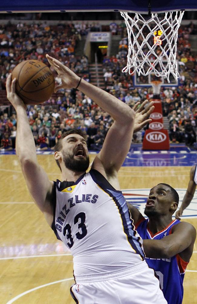 Memphis Grizzlies' Marc Gasol, left, of Spain, goes up for a shot against Philadelphia 76ers' Jarvis Varnado during the first half of an NBA basketball game, Saturday, March 15, 2014, in Philadelphia