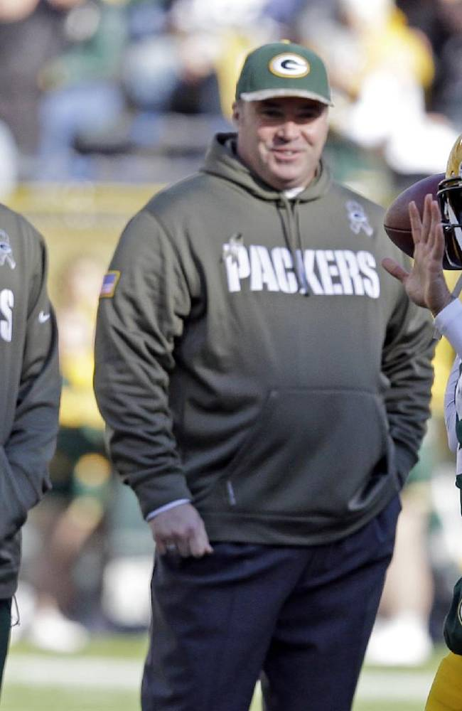 Green Bay Packers head coach Mike McCarthy and Aaron Rodgers watch as quarterback Seneca Wallace warms up before an NFL football game against the Philadelphia Eagles Sunday, Nov. 10, 2013, in Green Bay, Wis