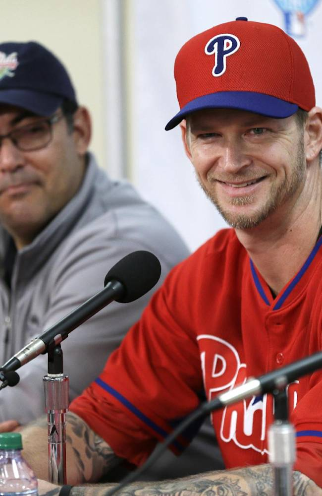 Philadelphia Phillies pitcher A.J. Burnett, right, speaks during a news conference as Phillies general manager Ruben Amaro Jr., left, looks on following a spring training baseball practice on Sunday, Feb. 16, 2014, in Clearwater, Fla