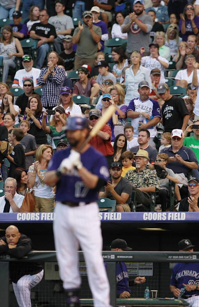 Fans stand to applaud as Colorado Rockies' Todd Helton steps to the plate to face the Arizona Diamondbacks in the first inning of a baseball game in Denver on Saturday, Sept. 21, 2013. Helton, who has played his entire 17-year career with the Rockies, has announced that he will retire at the conclusion of the 2013 season