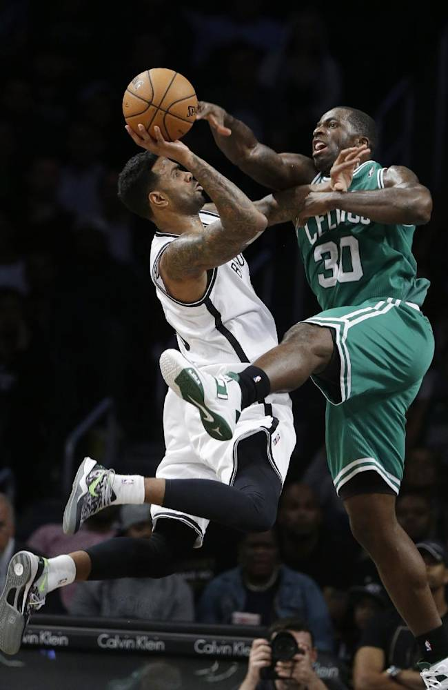 Brooklyn Nets' Gary Forbes, left, shoots as Boston Celtics' Brandon Bass, right, defends during the second half of a preseason NBA basketball game Tuesday, Oct. 15, 2013, in New York.  The Nets won 82-80