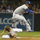 Los Angeles Dodgers shortstop Hanley Ramirez hurdles San Diego Padres' Tommy Medica while relaying to first to complete a double play in the seventh inning of the opening game of Major League baseball in the United States Sunday, March 30, 2014, in San Di