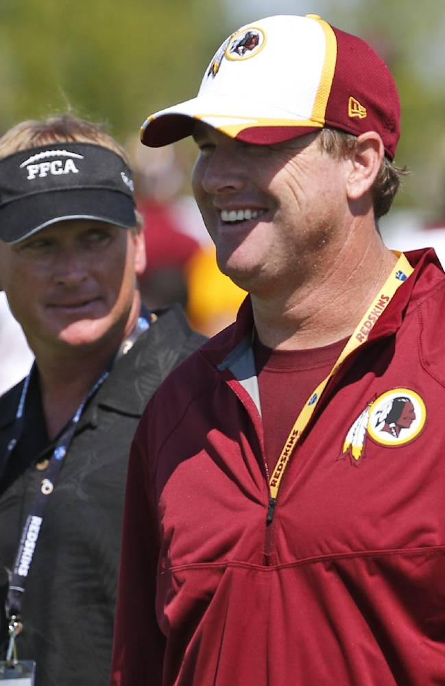 ESPN broadcaster and former NFL head coach Jon Gruden, left, walks with his brother, Washington Redskins head coach Jay Gruden, after practice at the team's NFL football training facility, Friday, July 25, 2014 in Richmond, Va. (AP Photo)