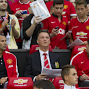 Manchester United's new manager Louis van Gaal, centre, takes his seat along side assistant manager Ryan Giggs, left, prior to his team's pre-season friendly soccer match, against Valencia at Old Trafford Stadium, Manchester, England, Tuesday Aug. 12, 20