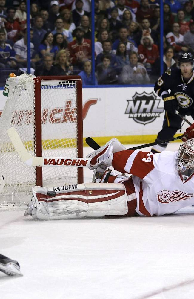Detroit Red Wings goalie Petr Mrazek, of the Czech Republic, stops a shot from St. Louis Blues' Maxim Lapierre (40) as Red Wings' Ryan Sproul (48) and Blues' Jordan Leopold (33) watch during the second period of an NHL hockey game Sunday, April 13, 2014, in St. Louis