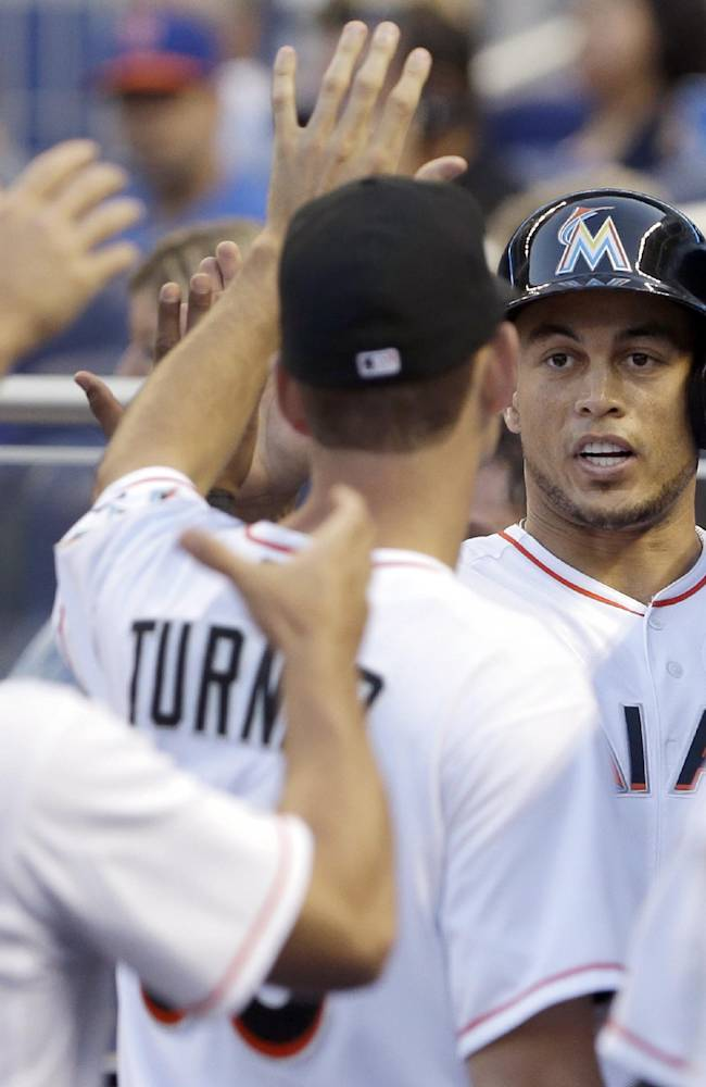 Miami Marlins' Giancarlo Stanton, right, is congratulated by teammates after Stanton scored on a single by Casey McGehee, during the first inning of a baseball game against the New York Mets, Tuesday, May 6, 2014, in Miami