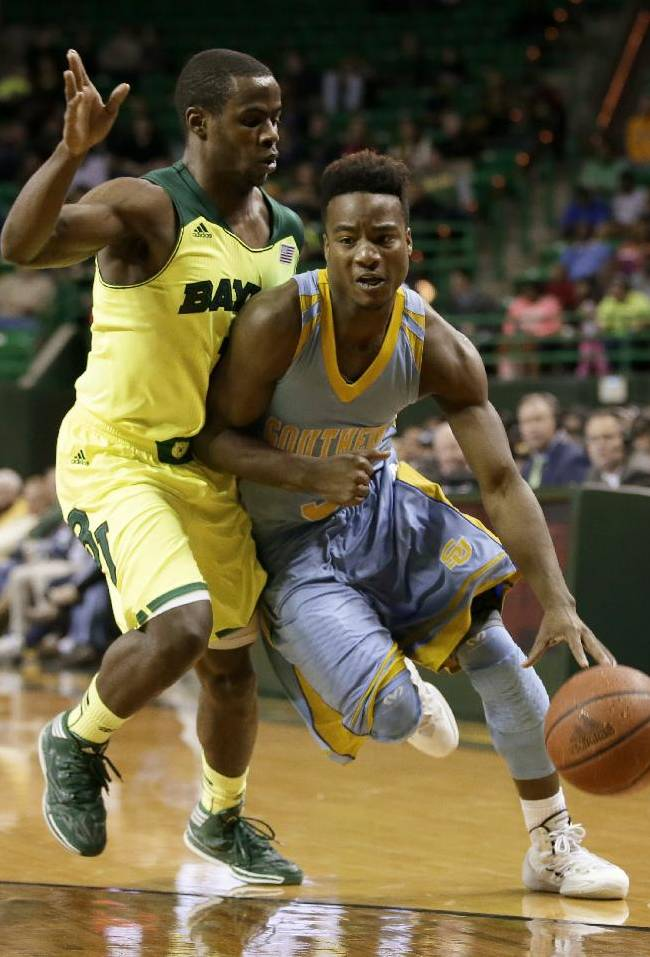 Baylor's Kenny Chery, defends as Southern's Trelun Banks drives to the basket in the first half of an NCAA college basketball game, Sunday, Dec. 22, 2013, in Waco, Texas