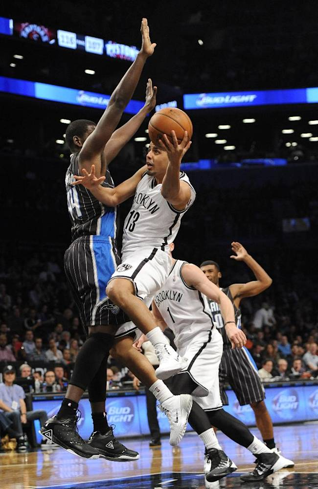 Brooklyn Nets' Jorge Gutierrez (13) takes aim for the basket around Orlando Magic's Andrew Nicholson (44) during the first half of an NBA basketball game Sunday, April 13, 2014, in New York