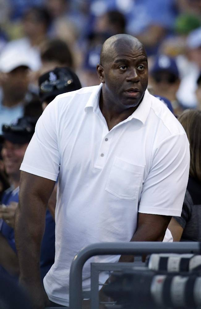 Los Angeles Dodgers owner Magic Johnson looks around during the eighth inning of Game 5 of the National League baseball championship series between the St. Louis Cardinals and the Los Angeles Dodgers, Wednesday, Oct. 16, 2013, in Los Angeles