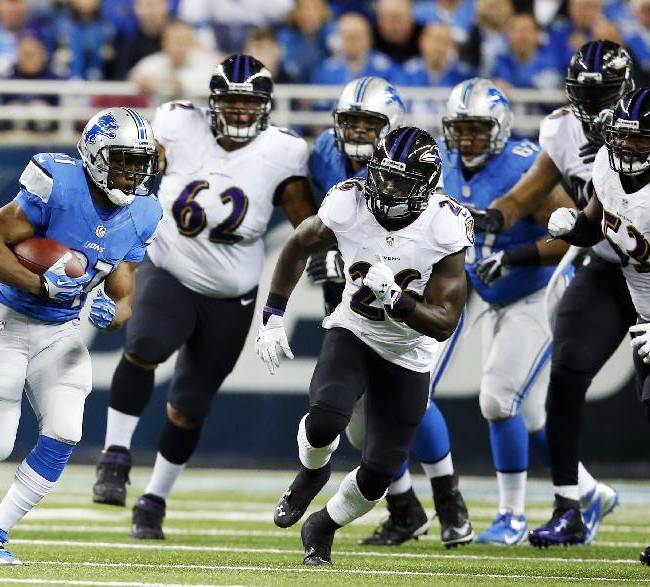 Detroit Lions running back Reggie Bush, left, pulls away from the Baltimore Ravens defense during the first quarter of an NFL football game in Detroit, Monday, Dec. 16, 2013
