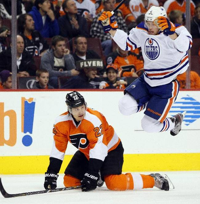 Edmonton Oilers' Taylor Hall, right, leaps to avoid Philadelphia Flyers' Luke Schenn, left, during the first period of an NHL hockey game, Saturday, Nov. 9, 2013, in Philadelphia