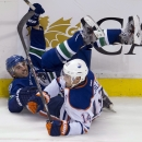 Vancouver Canucks defenceman Chris Tanev (8) and Edmonton Oilers right wing Jordan Eberle (14) go into the boards during the third period of NHL action in Vancouver, British Columbia Saturday, Oct. 11, 2014 The Associated Press