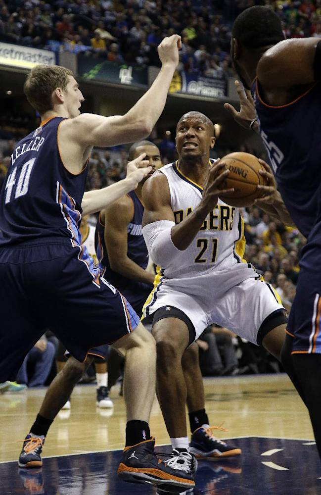 Indiana Pacers forward David West (21) drives through the lane between Charlotte Bobcats defenders Cody Zeller (40) and Al Jefferson, right, during the second half of an NBA basketball game in Indianapolis, Friday, Dec. 13, 2013. The Pacers won 99-94