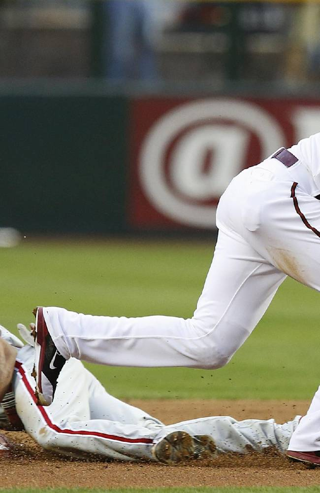 Philadelphia Phillies' Ben Revere (2) steals second base as Arizona Diamondbacks' Martin Prado makes a catch on a wide throw during the first inning of a baseball game on Friday, April 25, 2014, in Phoenix