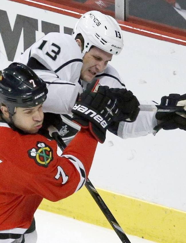 Chicago Blackhawks defenseman Brent Seabrook (7) and Los Angeles Kings left wing Kyle Clifford battle for a loose puck during the first period of an NHL hockey game Monday, Dec. 30, 2013, in Chicago