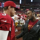 Injured Washington Redskins quarterback Robert Griffin III, right, talks with Arizona Cardinals quarterback Carson Palmer (3) after an NFL football game Sunday, Oct. 12, 2014, in Glendale, Ariz. The Cardinals defeated the Redskins 30-20 The Associated Pr