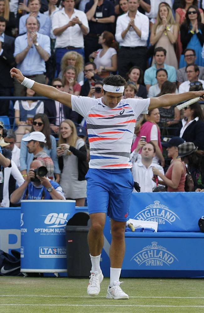 Marinko Matosevic of Australia celebrates his win against Jo-Wilfried Tsonga of France at the end of their Queen's Club grass court championships 3rd round tennis match in London, Thursday, June 12, 2014