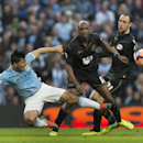 Manchester City's Sergio Aguero, left, is thwarted by Wigan's Emmerson Boyce, centre, as Ivan Ramis looks on during their English FA Cup quarterfinal soccer match at the Etihad Stadium, Manchester, England, Sunday, March 9, 2014