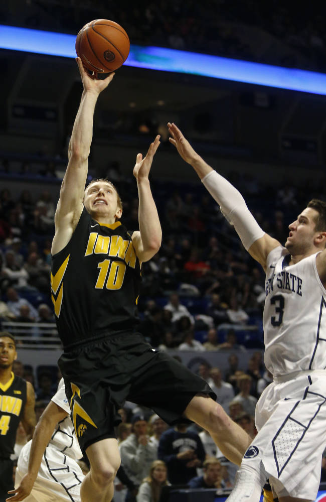 Iowa's Mike Gesell (10) shoots in front of Penn State's Graham Woodward (3) during the first half of an NCAA college basketball game on Saturday, Feb. 15, 2014, in State College. Iowa won 82-70