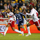 New York Red Bulls forward Thierry Henry (14) passes to forward Bradley Wright-Phillips (99) as Sporting Kansas City midfielder Jorge Claros (20) closes in during the second half in an MLS playoff soccer match at Red Bull Arena in Harrison, N.J., Thursday