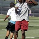 Washington Redskins quarterback Robert Griffin III celebrates with a youngster during a youth camp as part of the NFL football rookie symposium at the Cleveland Browns training facility in Berea, Ohio Tuesday, June 26, 2012. A former Baylor basketball player is facing a federal extortion charge for allegedly threatening to release 