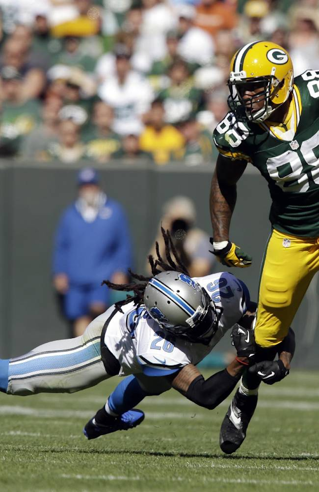 Detroit Lions' Louis Delmas (26) tries to stop Green Bay Packers' Jermichael Finley (88) after a catch during the first half of an NFL football game Sunday, Oct. 6, 2013, in Green Bay, Wis