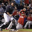 Philadelphia Phillies Marlon Byrd scores on Domonic Brown's sixth-inning, RBI single as New York Yankees catcher Brian McCann waits for the throw in a spring exhibition baseball game in Tampa, Fla., Tuesday, March 25, 2014 The Associated Press