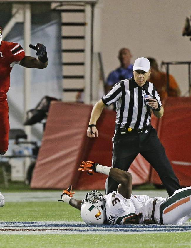 Louisville quarterback Teddy Bridgewater (5) leaps to avoid a tackle by Miami linebacker Thurston Armbrister during the second half of the Russell Athletic Bowl NCAA college football game in Orlando, Fla., Saturday, Dec. 28, 2013