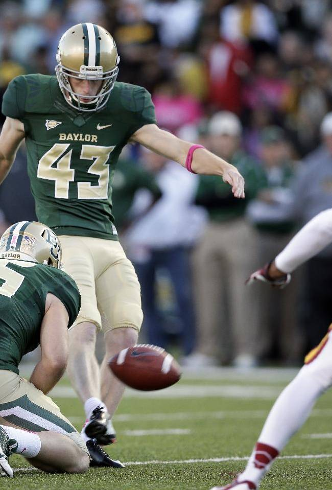 In this Oct. 19, 2013 photo, Baylor holder Brody Trahan (15) holds the ball as kicker Aaron Jones kicks an extra point under pressure from Iowa State defensive back Nigel Tribune (34) during an NCAA college football game in Waco, Texas. Baylor's explosive offense has been good to kicker Aaron Jones. After all those touchdowns come extra points. And Jones has just set the NCAA career mark for PATs