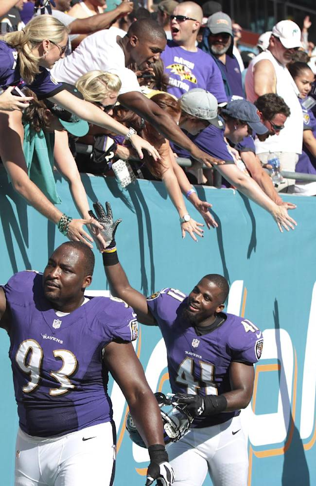 Baltimore Ravens players DeAngelo Tyson (93), Anthony Levine (41) and James Ihedigbo (32) celebrate with fans after an NFL football game against the Miami Dolphins, in Miami Gardens, Fla., Sunday, Oct. 6, 2013. The Ravens  won 26-23